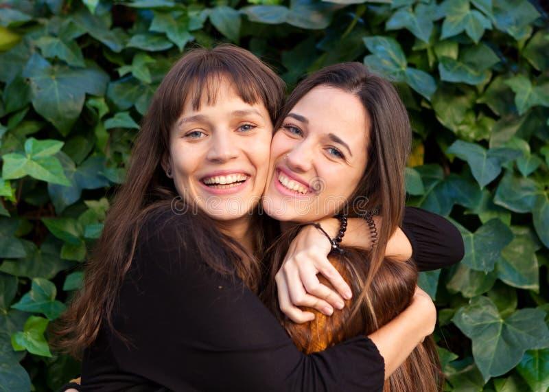Retrato al aire libre de dos hermanas felices en un parque fotos de archivo