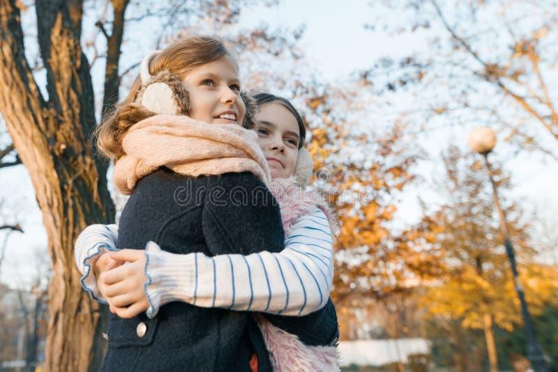 Retrato al aire libre de dos mejores amigos de las niñas, muchachas sonrientes que se abrazan que mira la puesta del sol, parque  foto de archivo
