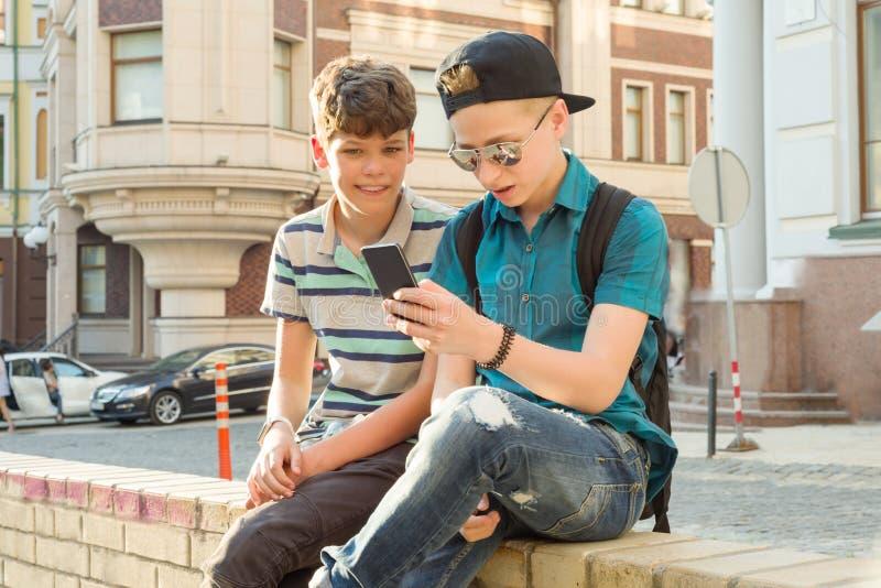 Retrato al aire libre de dos muchachos 13, 14 años, hablando en la calle de la ciudad, risa de los amigos, mirando el teléfono mó imagen de archivo
