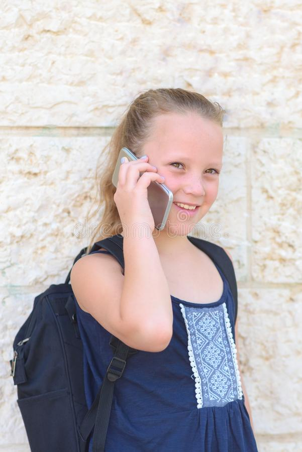 Retrato al aire libre de hablar de 8-9 a?os de la muchacha feliz en el tel?fono imagen de archivo