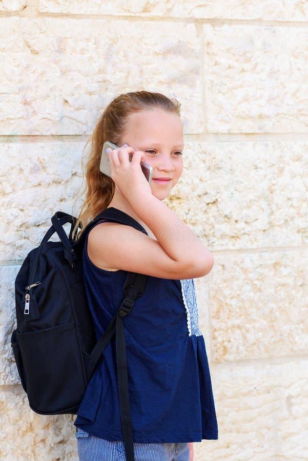 Retrato al aire libre de hablar de 8-9 a?os de la muchacha feliz en el tel?fono fotos de archivo libres de regalías