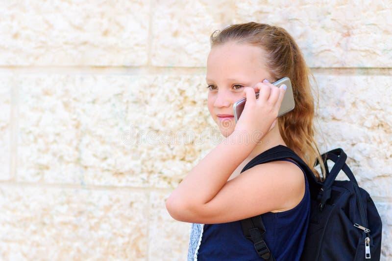 Retrato al aire libre de hablar de 8-9 a?os de la muchacha feliz en el tel?fono fotografía de archivo