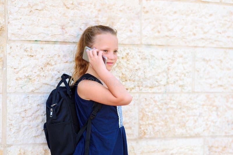 Retrato al aire libre de hablar de 8-9 a?os de la muchacha feliz en el tel?fono imágenes de archivo libres de regalías