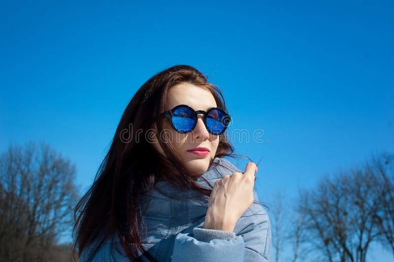 Retrato al aire libre de la chica joven que lleva las gafas de sol duplicadas y la ropa azules del invierno que presentan en el c fotografía de archivo libre de regalías