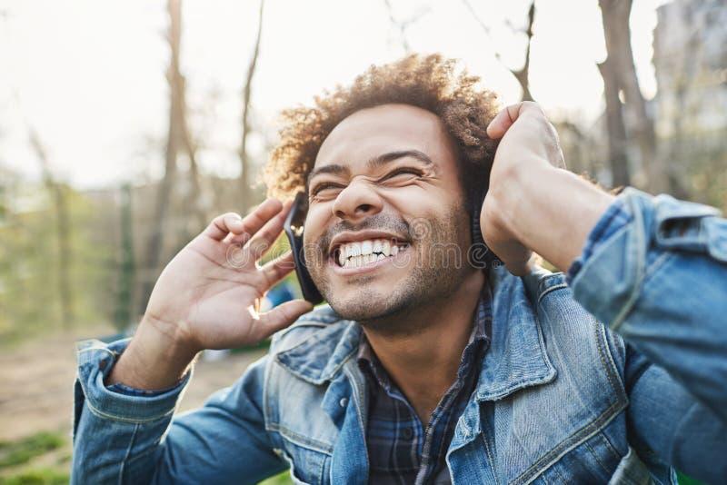 retrato al aire libre de la Lado-vista del hombre africano feliz emocionado con el peinado afro que sostiene los auriculares mien imagen de archivo libre de regalías