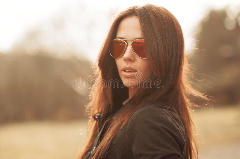 Retrato al aire libre de la moda de la mujer morena joven en gafas de sol fotografía de archivo