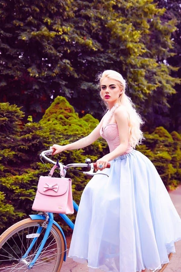 Retrato al aire libre de la moda de una muchacha rubia hermosa que completa un ciclo en el parque fotos de archivo