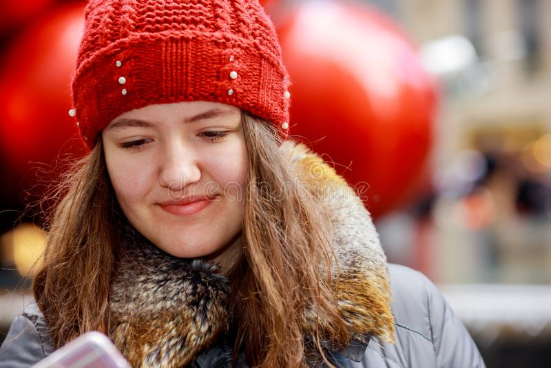 Retrato al aire libre de la muchacha preciosa joven hermosa que usa el teléfono móvil fotografía de archivo