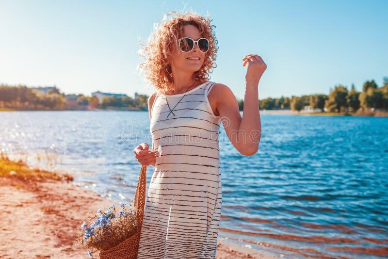 Retrato al aire libre de la mujer joven hermosa con el pelo rizado rojo que sostiene el bolso con las flores Equipo del verano foto de archivo libre de regalías