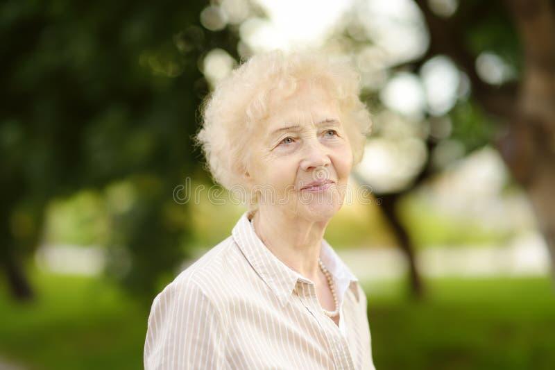 Retrato al aire libre de la mujer mayor hermosa con el pelo blanco rizado foto de archivo