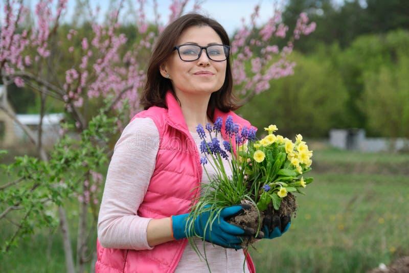 Retrato al aire libre de la mujer de mediana edad sonriente en guantes del jardín con las flores para plantar, fondo del jardín d foto de archivo