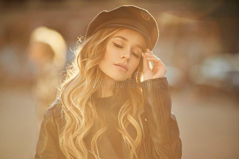 Retrato al aire libre de la mujer de moda y sensual hermosa joven en chaqueta de cuero negra y sombrero elegante con maquillaje y imagen de archivo