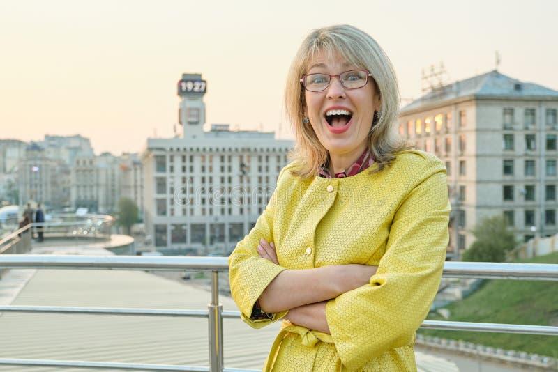 Retrato al aire libre de la mujer sonriente madura con los vidrios, chaqueta amarilla 40,45 años femeninos, fondo del parque de l imagen de archivo