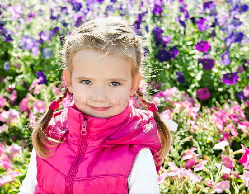Retrato al aire libre de la niña cerca de las flores fotografía de archivo