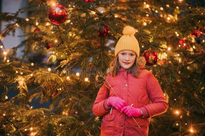 Retrato al aire libre de la niña al lado del árbol de navidad imagen de archivo libre de regalías