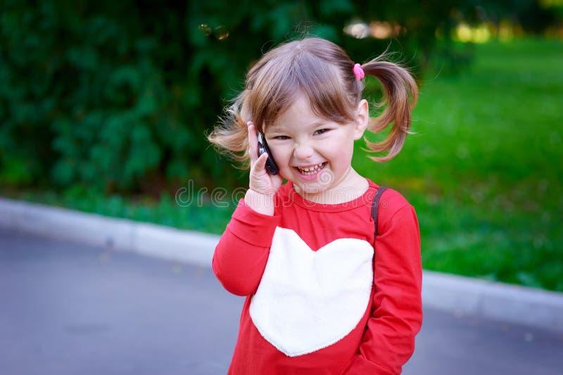 Retrato al aire libre de la niña linda que habla por el teléfono fotos de archivo