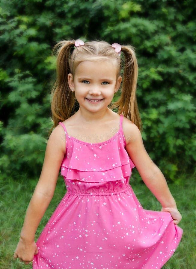 Retrato al aire libre de la niña sonriente que sostiene la flor imagen de archivo