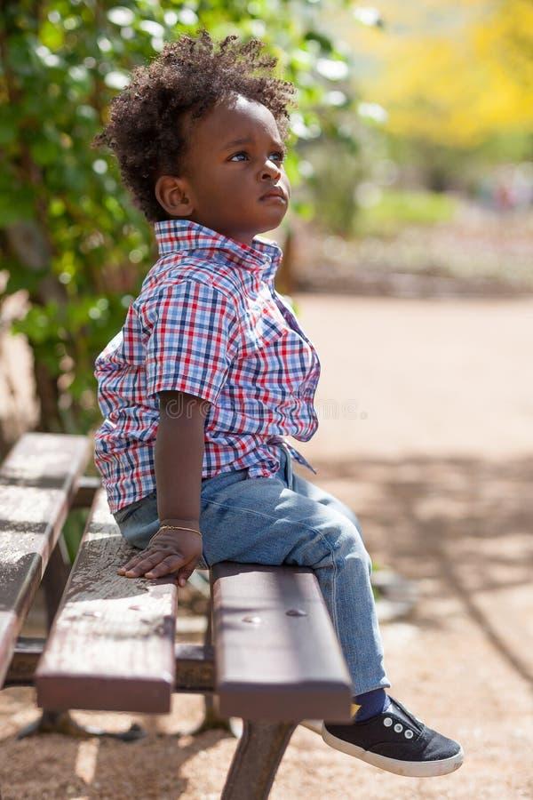 Retrato al aire libre de un bebé negro localizado en un banco fotos de archivo