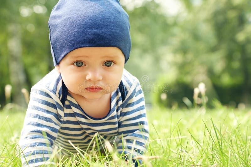 Retrato al aire libre de un beb? en todos los fours arrastre en niño de las rodillas en la hierba en parque del verano foto de archivo