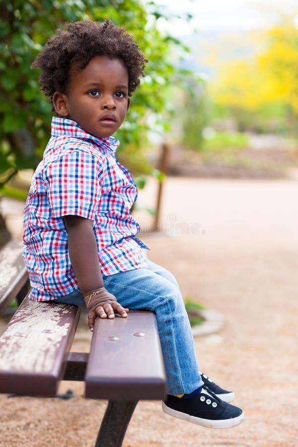Retrato al aire libre de un niño pequeño negro localizado en un banco imagenes de archivo