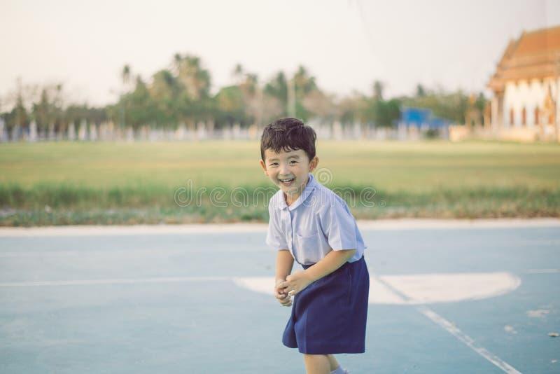 Retrato al aire libre de un ni?o asi?tico feliz del estudiante en la sonrisa del uniforme escolar imagen de archivo