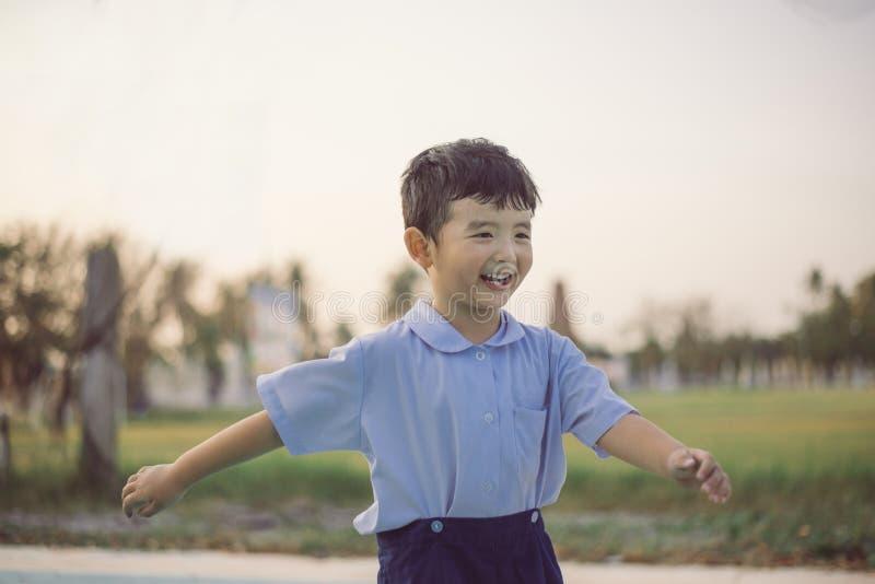 Retrato al aire libre de un ni?o asi?tico feliz del estudiante en la sonrisa del uniforme escolar fotos de archivo libres de regalías