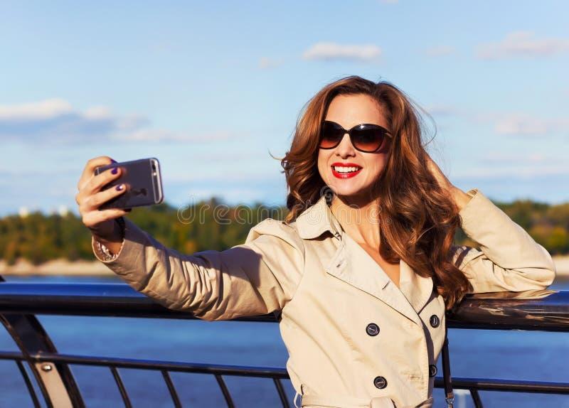 Retrato al aire libre de una muchacha hermosa joven que toma un selfie usando su teléfono imagenes de archivo