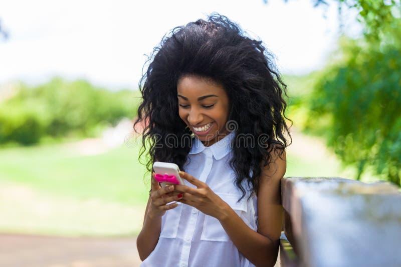 Retrato al aire libre de una muchacha negra adolescente que usa un teléfono móvil - fotos de archivo