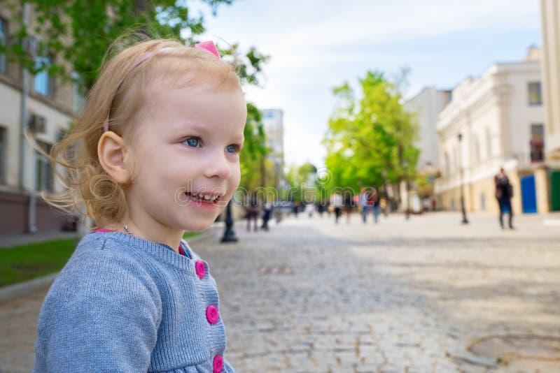 Retrato al aire libre de una niña linda en una ciudad, sonriendo imagen de archivo
