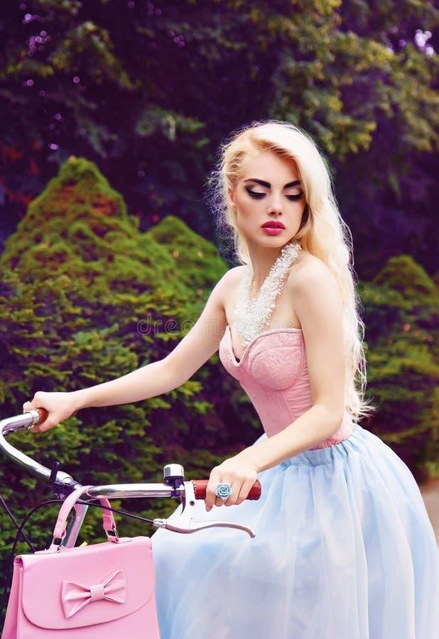 Retrato al aire libre del encanto de una muchacha rubia atractiva que monta una bicicleta en el parque fotografía de archivo libre de regalías