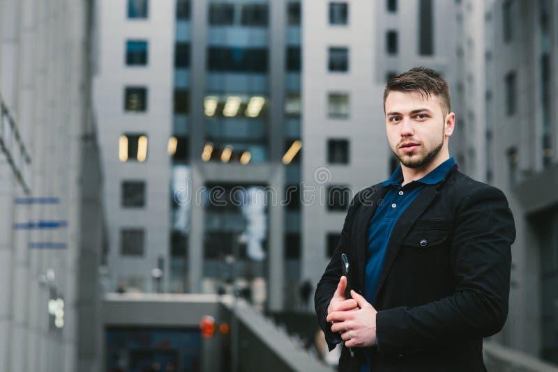 Retrato al aire libre del hombre de negocios joven con un Tablet PC en las manos contra la perspectiva del centro de negocios imagen de archivo