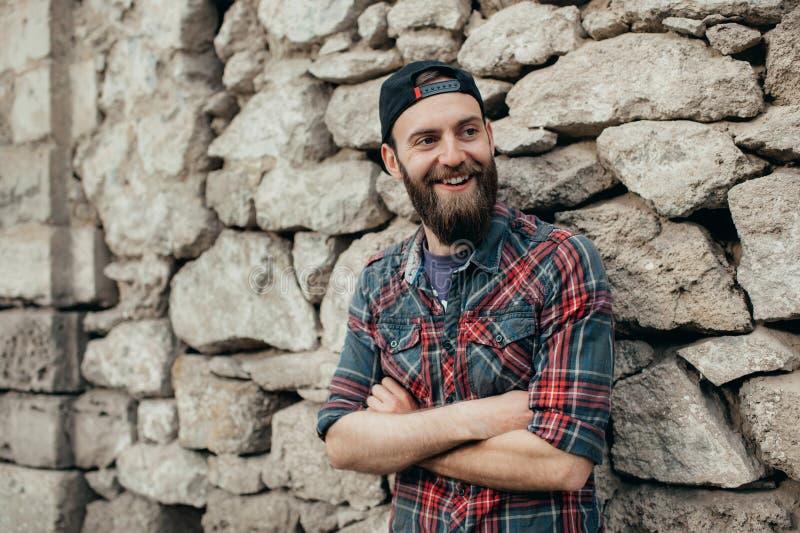 Retrato al aire libre del hombre sonriente hermoso joven con la barba sobre el fondo de piedra foto de archivo libre de regalías