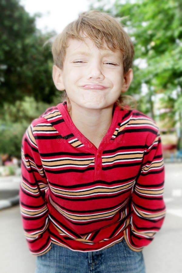 Retrato al aire libre del muchacho del niño que hace caras imagenes de archivo
