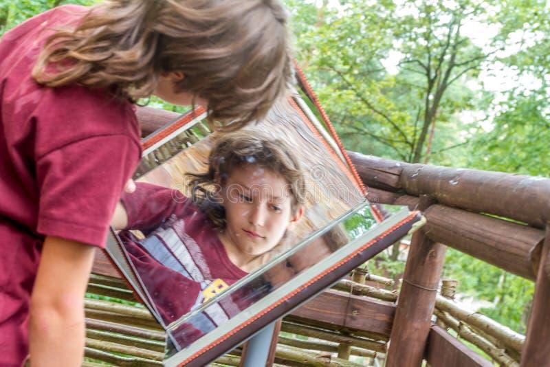 Retrato al aire libre del muchacho joven que mira y reflejado en espejo fotografía de archivo libre de regalías