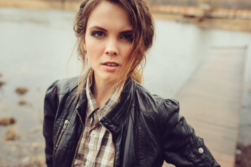 Retrato al aire libre del otoño de la mujer hermosa joven con maquillaje natural en la chaqueta de cuero y la camisa de tela esco foto de archivo libre de regalías