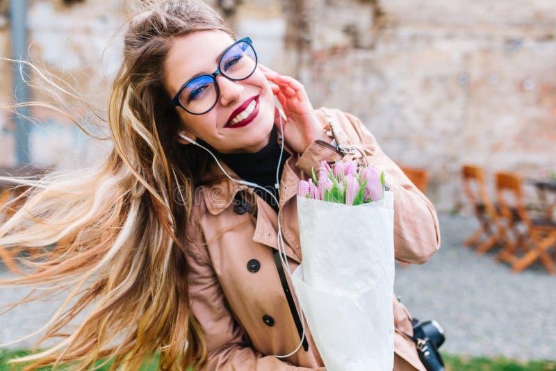 Retrato al aire libre del primer de la muchacha sonriente preciosa con el pelo largo y los tulipanes que fluyen rubios que llevan imagen de archivo