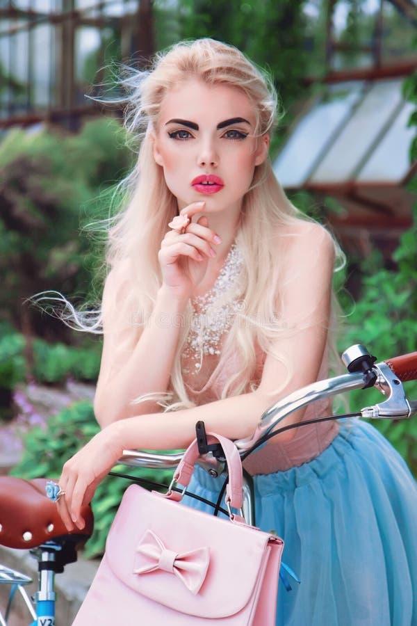 Retrato al aire libre del primer de una muchacha rubia muy hermosa y dulce con una bicicleta imágenes de archivo libres de regalías