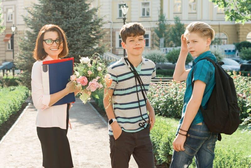 Retrato al aire libre del profesor de escuela con el ramo de flores y el grupo de alumnos adolescentes Los niños felicitan su fotos de archivo