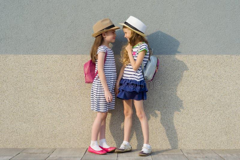 Retrato al aire libre del verano de dos amigas felices 7,8 años en el perfil que habla y que ríe Muchachas en los vestidos rayado imágenes de archivo libres de regalías