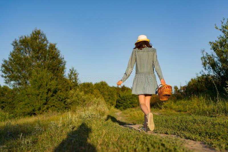 Retrato al aire libre del verano de la muchacha adolescente con las fresas de la cesta, sombrero de paja Una muchacha en la carre fotos de archivo