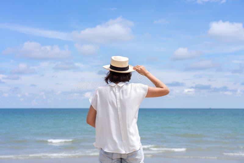 Retrato al aire libre del verano de la mujer asiática joven que lleva el sombrero elegante y la ropa que se colocan en la playa,  fotos de archivo