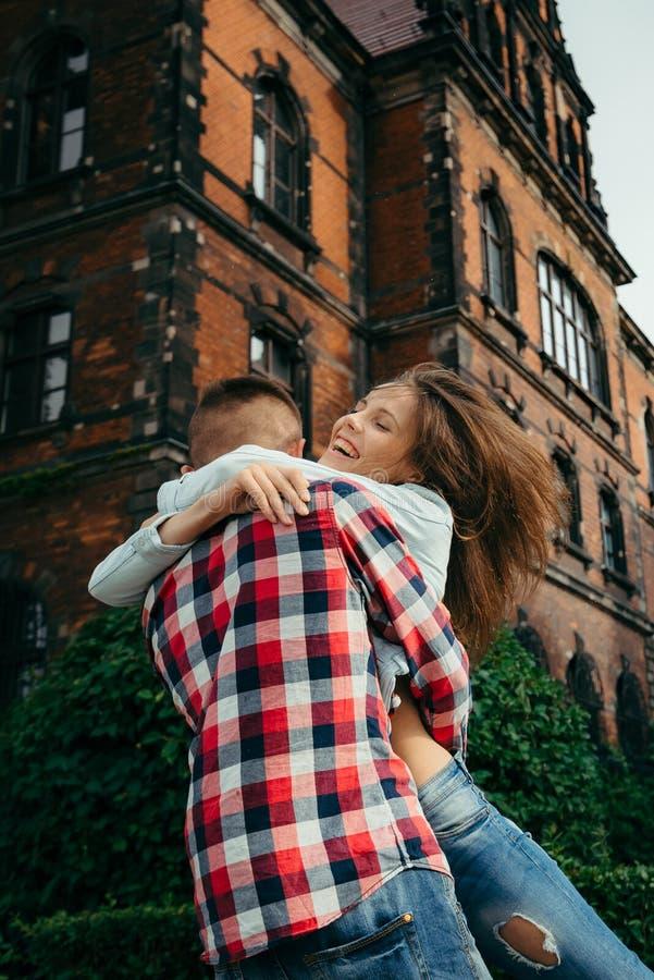 Retrato al aire libre emocional de la muchacha hermosa feliz La opinión trasera el hombre que la abraza y que levanta para arriba foto de archivo