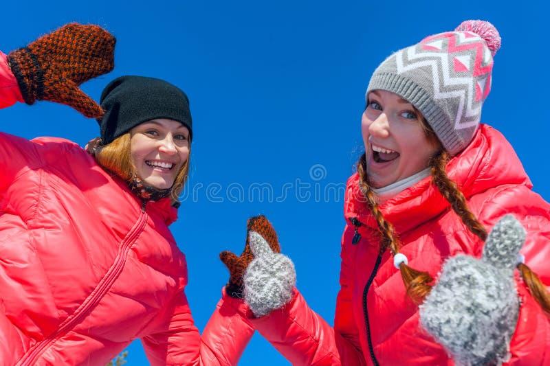 Retrato al aire libre Muchacha feliz joven dos que juega en la nieve en la nieve del invierno Paseo en la parte de atrás de uno a fotografía de archivo