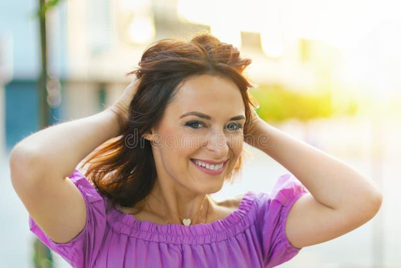 Retrato al aire libre Mujer hermosa joven que visita un centro de ciudad durante un día soleado, sonriendo en la cámara con los e foto de archivo