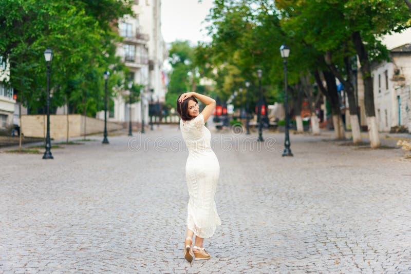Retrato al aire libre Mujer hermosa joven que visita un centro de ciudad durante un día soleado, sonriendo en la cámara con los e imagenes de archivo