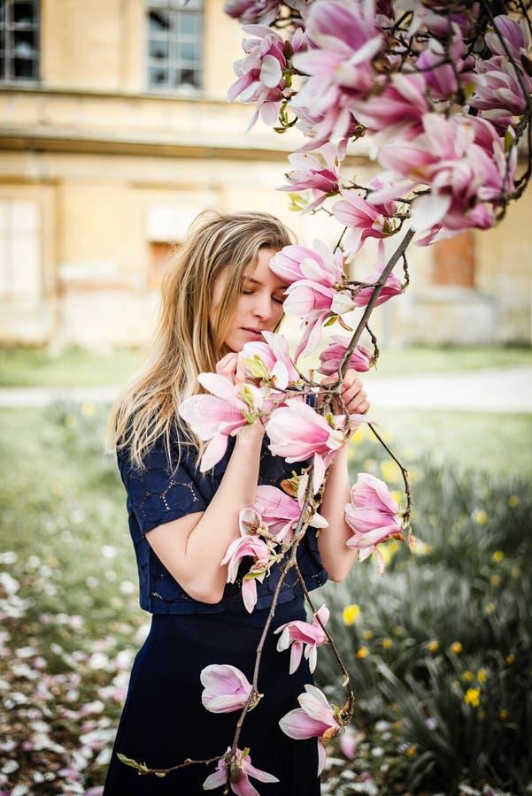 Retrato al aire libre rom?ntico de la mujer de moda joven que presenta con el ?rbol de la magnolia en la floraci?n foto de archivo libre de regalías