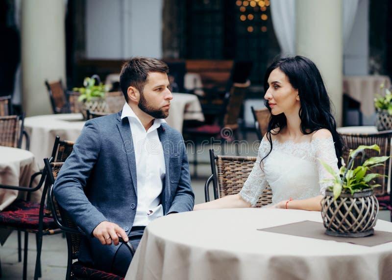 Retrato al aire libre romántico de los pares de la boda que miran uno a mientras que se sienta en la tabla del restaurante imagen de archivo