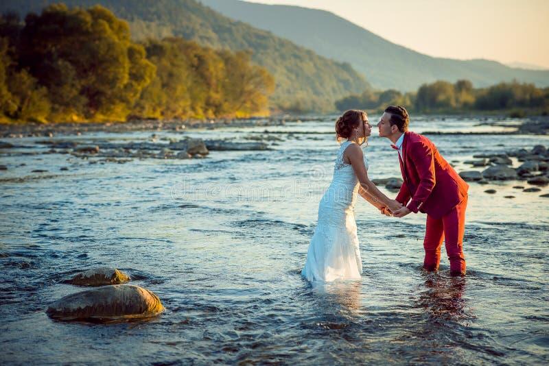 Retrato al aire libre romántico de los recienes casados hermosos que llevan a cabo las manos y que van a besarse mientras que se  fotos de archivo libres de regalías