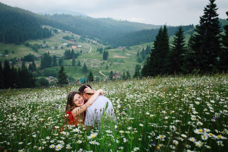 Retrato al aire libre romántico La mujer sonriente rubia magnífica está abrazando feliz a su novio mientras que se sienta en el c fotos de archivo