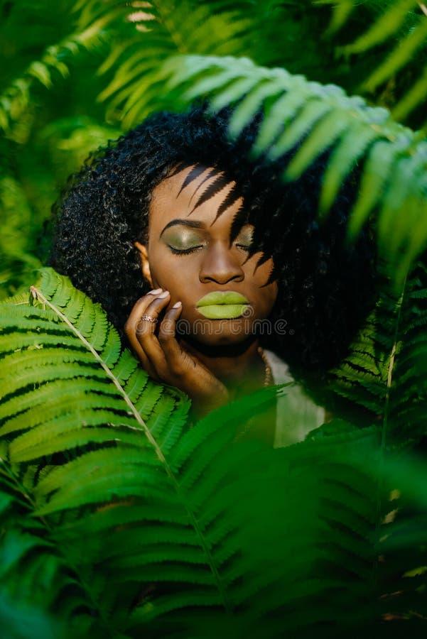 Retrato al aire libre sensible de la muchacha africana atractiva con el lápiz labial verde y los sombreadores de ojos que tocan s fotografía de archivo